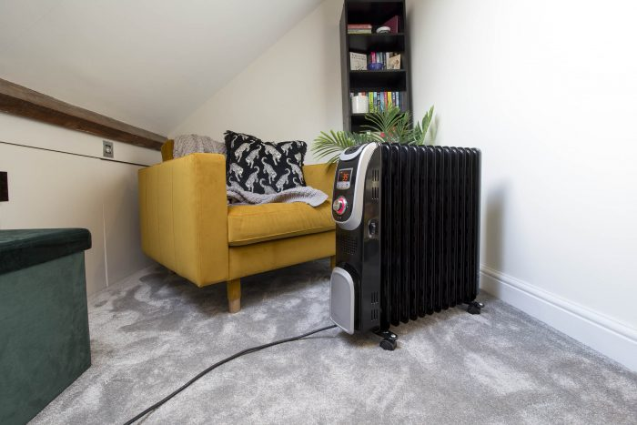 Oil filled radiator near a reading chair