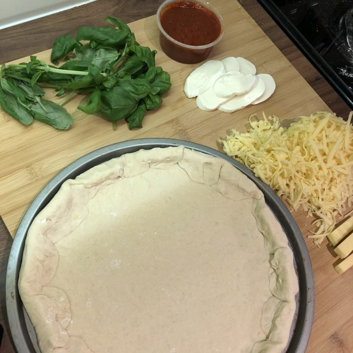 Pizza dough with ingredients next to it